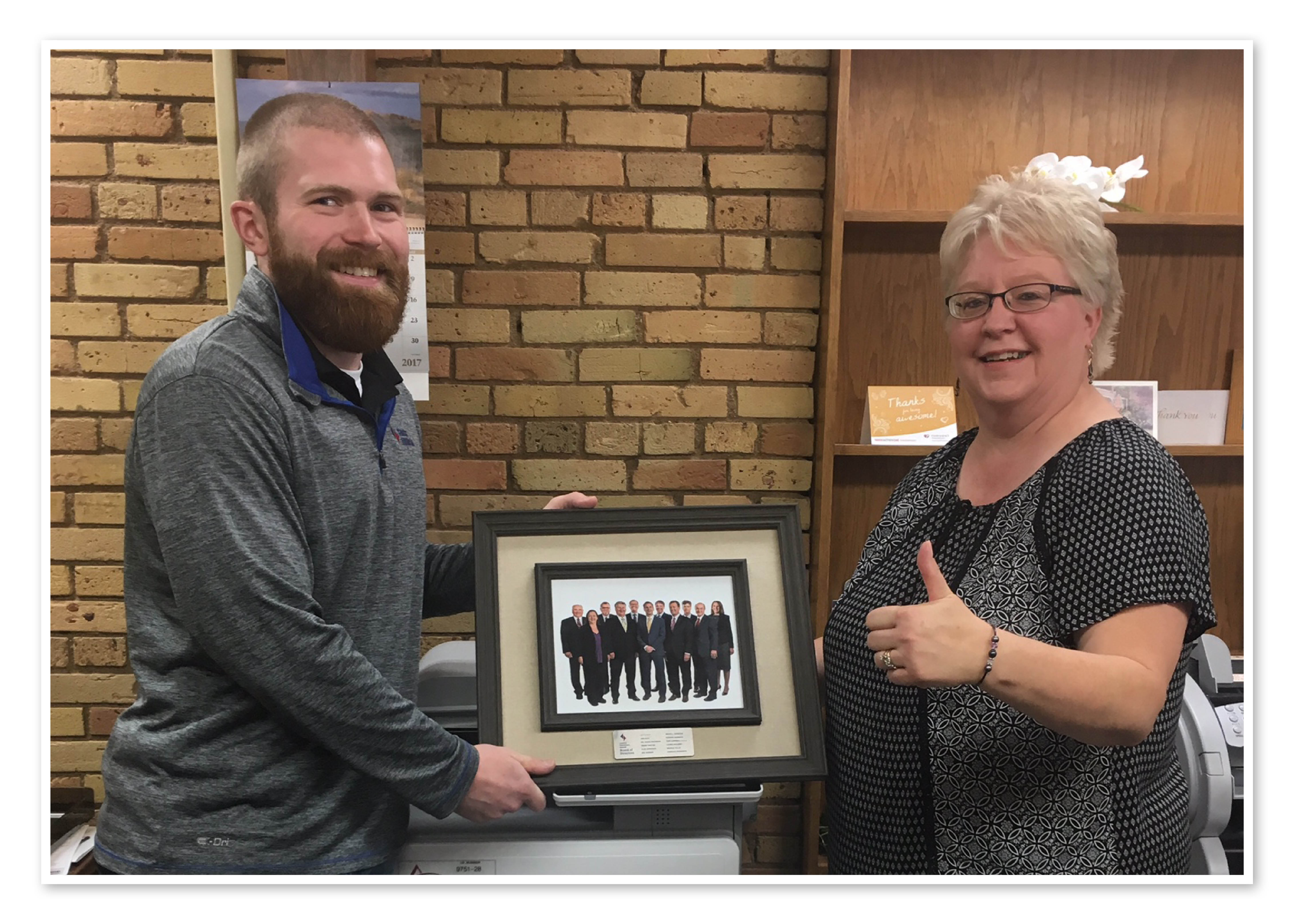Todd and Karen hold the picture of the board of directors, ready to be hung on the wall. Karen gives a thumbs up.