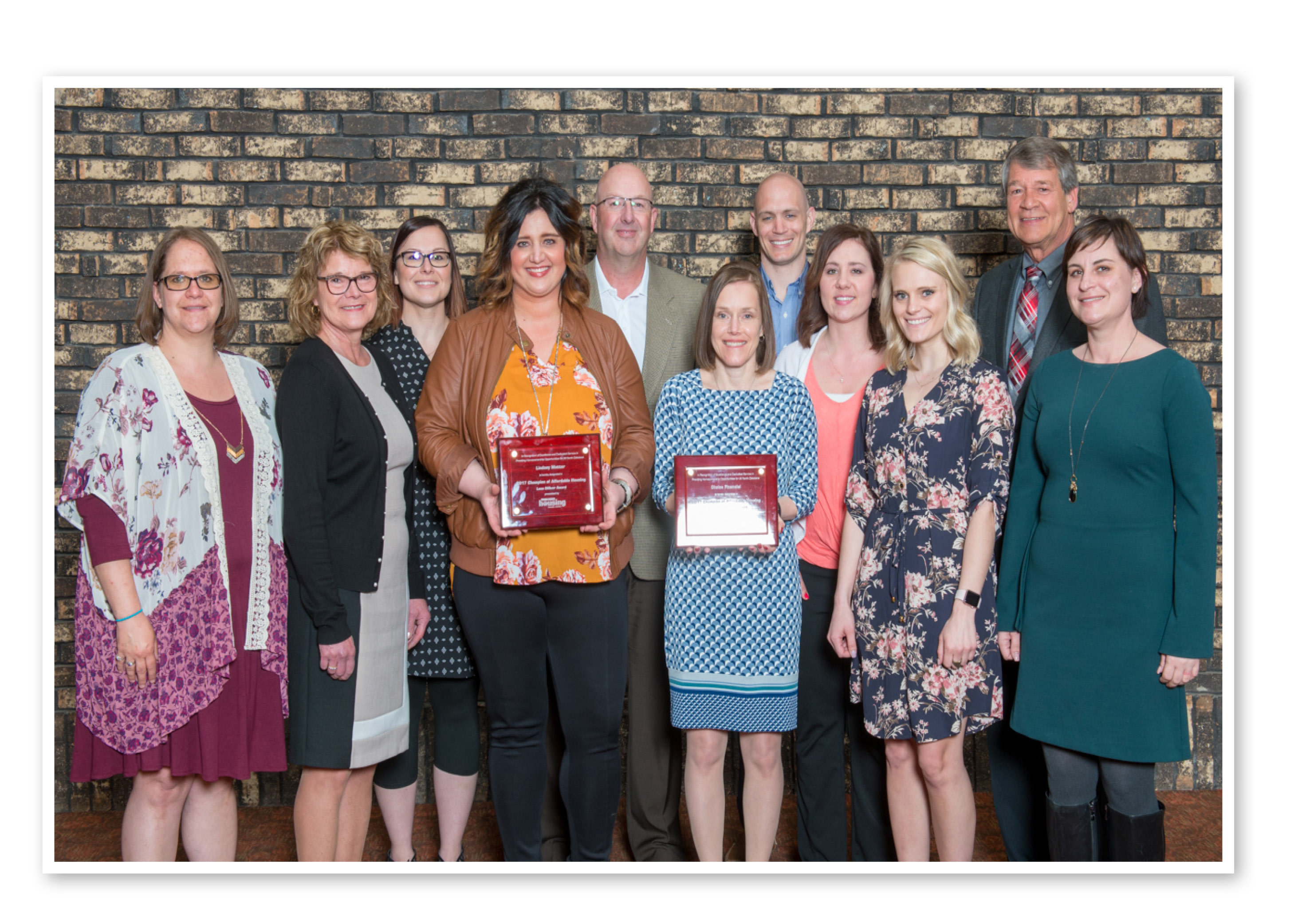 Representatives from the Choice mortgage team accepting the Champion award. (left to right) Shawna Eckroth, Jolene Kline (Executive Director of NDHFA), Tosha Steinwand, Lindsey Matter, Greg Schwab, Susie Franklin, Blair Sandy, Terri Mollman, Shania Gross, Wayne Stenehjem (ND Attorney General), Celeste Burke