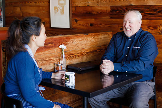 Bob sitting at a table with customer.