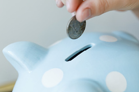 Hand putting a coin into a piggy bank.