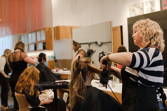 Woman blow drying another woman's hair at a salon.