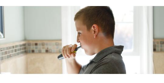 Boy brushing teeth.