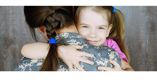 Military mother hugging her daughter goodbye.